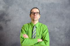 Bedrijfsmens in groen overhemd en stropdas met gekruiste wapens Royalty-vrije Stock Fotografie