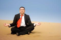 Bedrijfsmens het ontspannen en gaat zitten op het zand Royalty-vrije Stock Afbeeldingen