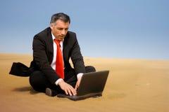 Bedrijfsmens het ontspannen en gaat zitten op het zand Stock Fotografie