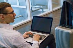 Bedrijfsmens in het witte werken aan laptop die WiFi Internet in luchthaven gebruiken stock foto