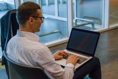 Bedrijfsmens in het witte werken aan laptop die WiFi Internet in luchthaven gebruiken stock foto's