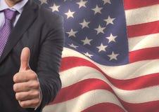 Bedrijfsmens met duimen omhoog tegen Amerikaanse vlag Stock Fotografie