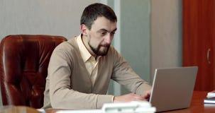 Bedrijfsmens met een baard die een videopraatje in zijn bureau hebben stock videobeelden