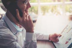 Bedrijfsmens met glazen die zwarte mobiele telefoon met behulp van stock foto