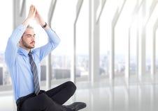 Bedrijfsmens met handen het lucht mediteren met gloed tegen onscherp wit venster Stock Foto's