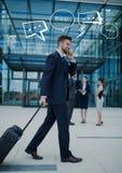 Bedrijfsmens met koffer op telefoon met witte toespraakbellen Stock Afbeeldingen