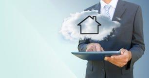 Bedrijfsmens met tablet en wolk met huis tegen blauwe achtergrond Stock Foto's