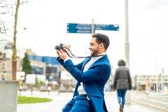 Bedrijfsmens op blauw kostuum die een beeld in openlucht nemen stock foto