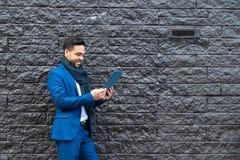 Bedrijfsmens op blauw kostuum die een tablet gebruiken royalty-vrije stock afbeeldingen