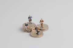 Bedrijfsmens op de bovenkant van muntstukkenstapel Stock Foto