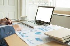 Bedrijfsmens op kantoor met laptop werken, en financiële grafiek die Stock Fotografie