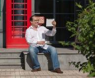 Bedrijfsmens op rode klassieke Engelse telefooncel Stock Afbeelding