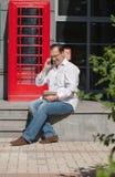 Bedrijfsmens op rode klassieke Engelse telefooncel Stock Afbeeldingen