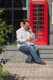 Bedrijfsmens op rode klassieke Engelse telefooncel Royalty-vrije Stock Foto