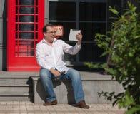 Bedrijfsmens op rode klassieke Engelse telefooncel Stock Fotografie