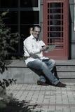 Bedrijfsmens op rode klassieke Engelse telefooncel Stock Foto