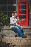 Bedrijfsmens op rode klassieke Engelse telefooncel Royalty-vrije Stock Afbeelding