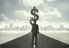 Bedrijfsmens op wegrubriek naar een dollarteken Royalty-vrije Stock Foto