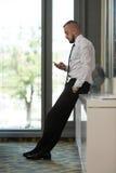 Bedrijfsmens Texting op Cellphone in Modern Bureau Stock Afbeelding