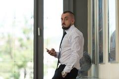 Bedrijfsmens Texting op Cellphone in Modern Bureau Stock Afbeeldingen
