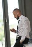 Bedrijfsmens Texting op Cellphone in Modern Bureau Royalty-vrije Stock Afbeeldingen