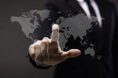 Bedrijfsmens wat betreft het denkbeeldige scherm met wereldkaart Royalty-vrije Stock Fotografie