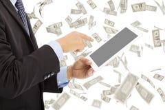 Bedrijfsmens wat betreft tablet met de achtergrond van de geldregen Royalty-vrije Stock Fotografie