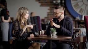 Bedrijfsmensen bij middagpauze in een koffie Twee mannen en een vrouwenbespreking over het werk tijdens lunch Mooie jonge mensen stock video