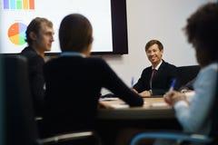 Bedrijfsmensen in Bureauvergaderzaal met Grafieken op TV Stock Foto