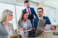 Bedrijfsmensen die aan bedrijfsproject in bureau werken die laptop met behulp van stock afbeeldingen