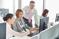 Bedrijfsmensen die aan computer in bureau werken Stock Fotografie