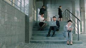 Bedrijfsmensen die aan trappen door de bureaubouw werken die verschillende gadgets gebruiken stock video