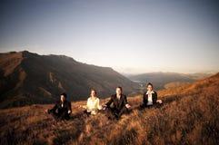 Bedrijfsmensen die Bergen mediteren stock foto's