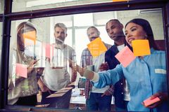 Bedrijfsmensen die bij bureau en gebruikspost-itnota's samenkomen om idee te delen Hersenen en flitsen Kleverige nota over glasmu stock fotografie