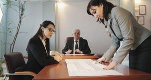 Bedrijfsmensen die bij de bestuurskamer zitten en zaken-plan bespreken stock footage