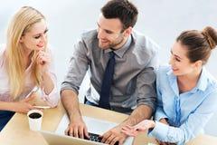 Bedrijfsmensen die bij lijst samenkomen Stock Foto