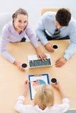 Bedrijfsmensen die bij lijst samenkomen Stock Foto's