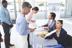 Bedrijfsmensen die binnen bij de lijst van de conferentieregistratie controleren stock afbeeldingen