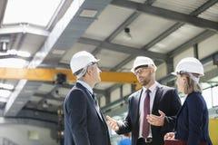 Bedrijfsmensen die bouwvakkers dragen die bespreking in de metaalindustrie hebben stock fotografie
