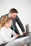 Bedrijfsmensen die in bureau met computer samenwerken Stock Foto's