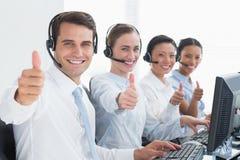 Bedrijfsmensen die camera met omhoog duimen bekijken Stock Foto's