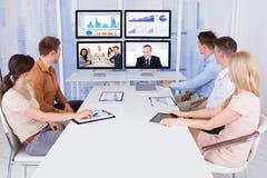 Bedrijfsmensen die computermonitors bekijken in bureau Royalty-vrije Stock Foto's