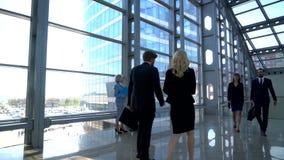 Bedrijfsmensen die in de bureaubouw lopen