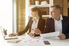 Bedrijfsmensen die de grafieken en de grafieken bespreken die onderzoek tonen royalty-vrije stock afbeeldingen