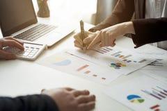 Bedrijfsmensen die de grafieken en de grafieken bespreken die onderzoek tonen stock foto's