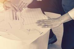 Bedrijfsmensen die de grafieken en de grafieken bespreken die onderzoek tonen stock afbeelding