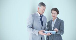 Bedrijfsmensen die digitale tablet over grijze achtergrond gebruiken Royalty-vrije Stock Foto