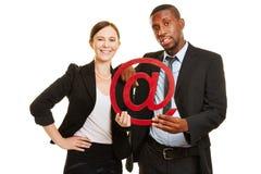 Bedrijfsmensen die e-mailsymbool houden Stock Foto's