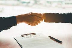 Bedrijfsmensen die een contracthanddruk tussen col. twee bespreken royalty-vrije stock foto