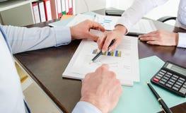Bedrijfsmensen die een grafiek analyseren Stock Foto's